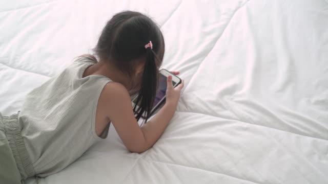 vídeos y material grabado en eventos de stock de niña acostada en la cama usando el teléfono móvil - nativo digital