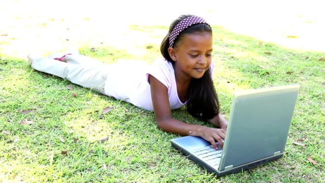stockvideo's en b-roll-footage met little girl lying on grass using laptop - 8 9 jaar