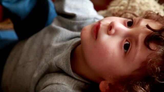 vidéos et rushes de petite fille allongée sur le dos et rêverie - curiosité