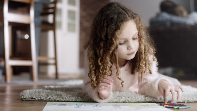 Little girl lying on the floor and drawing