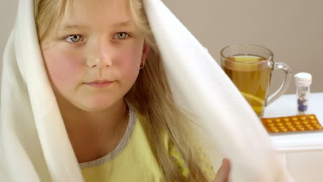 vídeos de stock, filmes e b-roll de menina deitada doente na cama dela, bebendo chá quente. - tossindo