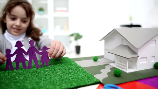 hd: little girl making and playing with paper doll family. - architectural model stock videos and b-roll footage