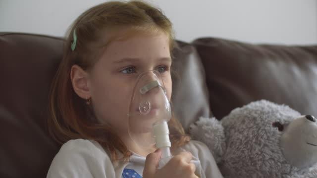 vídeos de stock e filmes b-roll de little girl making inhalation - asmático