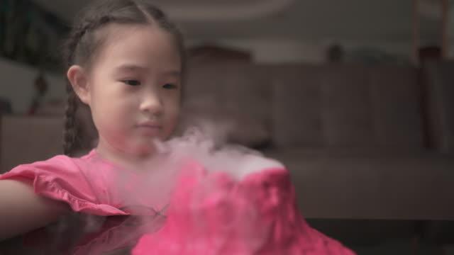 liten flicka gör vulkan för lärande vetenskap hemma. homeschool - vulkan bildbanksvideor och videomaterial från bakom kulisserna