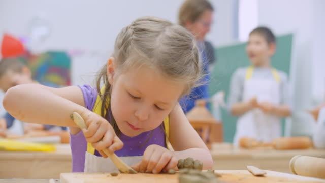 vídeos y material grabado en eventos de stock de niña moldeando arcilla en el aula - arcilla
