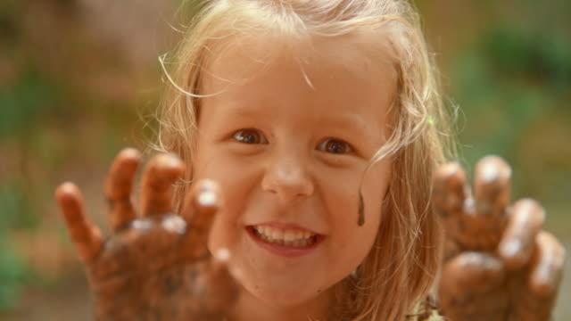 slo mo 少女カメラ一面に泥を塗りつける彼女泥手と近い脅しを移動 - ヨゴレ点の映像素材/bロール