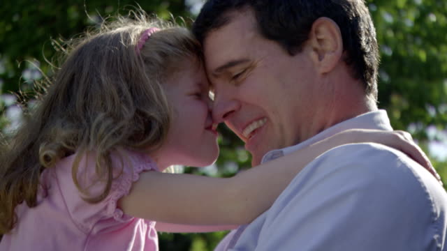 a little girl nuzzles her father as he holds her. - daughter stock videos and b-roll footage
