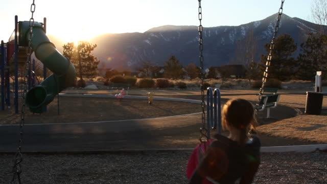 Little girl on a swings set