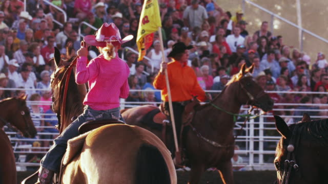 vídeos y material grabado en eventos de stock de little girl on her horse with a group perform a routine at a rodeo while spectators watch - shot in slow motion. - un minuto o más