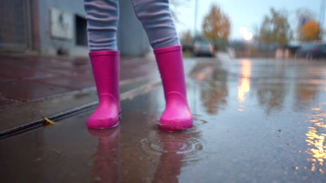 vídeos de stock e filmes b-roll de little girl on rain in boots standing in puddle - ficar de pé