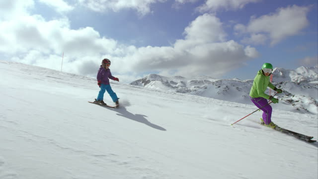 ts little girl on skis skiing behind her ski instructor - winter sport stock videos and b-roll footage