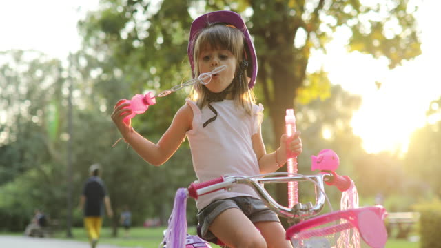 little girl on the bike blowing bubbles - soap sud stock videos & royalty-free footage