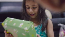 A little girl opening gift box.
