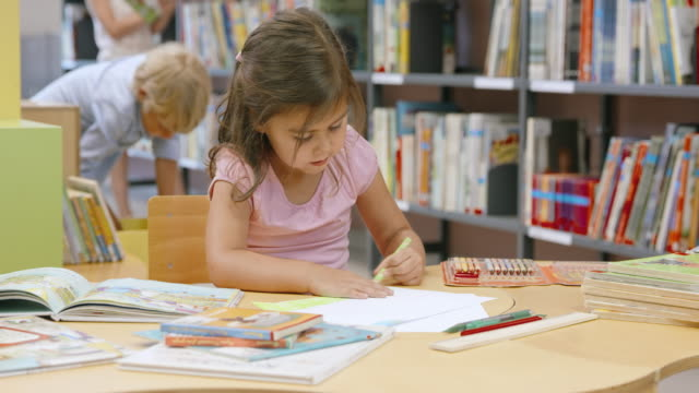 DS Little girl painting a drawing in library