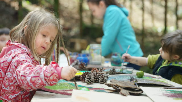 little girl painting at the creative workshop held in a forest - pinecone stock videos & royalty-free footage