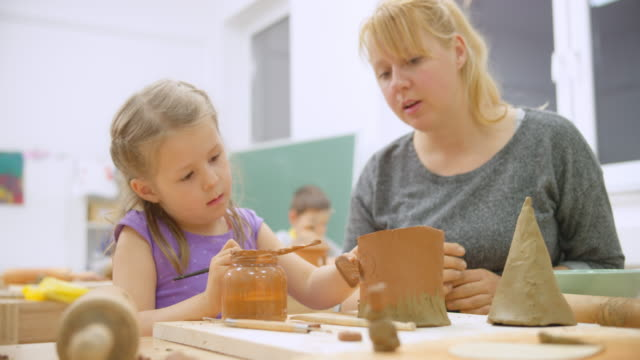 little girl painting her ceramic birdhouse and her teacher helping - elementary age stock videos & royalty-free footage