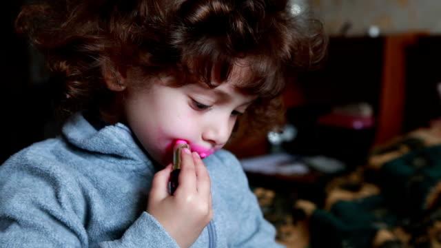 Little girl painting her lips with broken lipstick