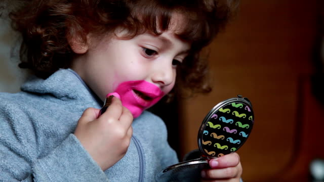 little girl painting her lips with lipstick and looking at pocket mirror - make up stock videos and b-roll footage
