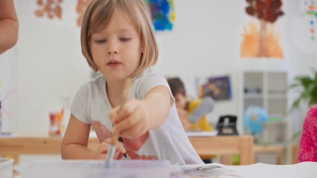 ds little girl painting in the bright classroom - malen stock-videos und b-roll-filmmaterial