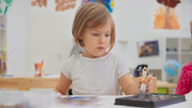 ds little girl painting in the classroom using a large paintbrush - art class stock videos & royalty-free footage