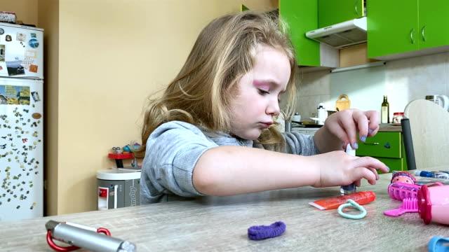小さな女の子は子供のマニキュアで爪を塗ります。 - マニキュア液点の映像素材/bロール