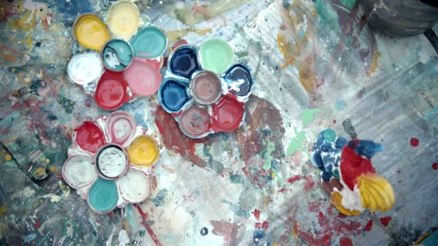 vidéos et rushes de cu: petite fille peintures sur papier utilisent palette, pinceau et peinture acrylique. - métier d'art