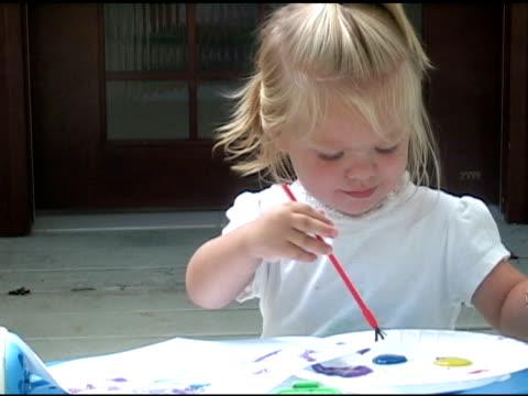 little girl paints with the color blue. - endast flickor bildbanksvideor och videomaterial från bakom kulisserna
