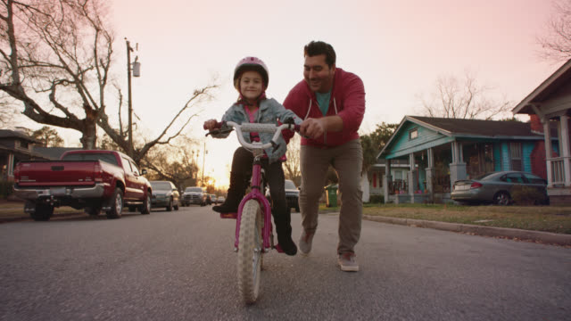 WS SLO MO. Little girl pedals bike and smiles at camera as dad runs alongside on neighborhood street.