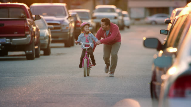 WS SLO MO. Little girl pedals bike down neighborhood street as dad runs alongside teaching her how to ride.