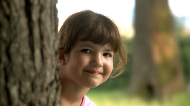 little girl peeking from behind tree - hide and seek stock videos & royalty-free footage