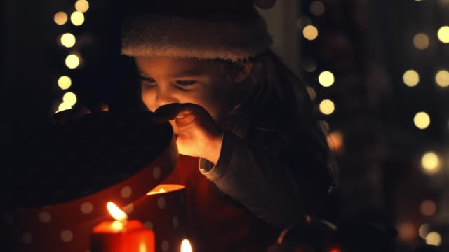 vídeos de stock e filmes b-roll de little girl peeking in her christmas gift box - chapéu