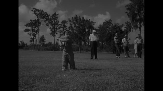 little girl picks up ball out of hole / children run to registration tent / children register with man / boy tees off / cu girl / girl tees off /... - golf shoe stock videos & royalty-free footage
