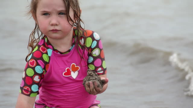 ms little girl piling up mound of sand in her hand on beach at water break / toronto, ontario, canada - kelly mason videos stock videos & royalty-free footage