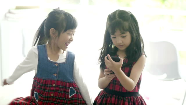 2 little girl playing a mobile phone - 6 7 years stock videos & royalty-free footage