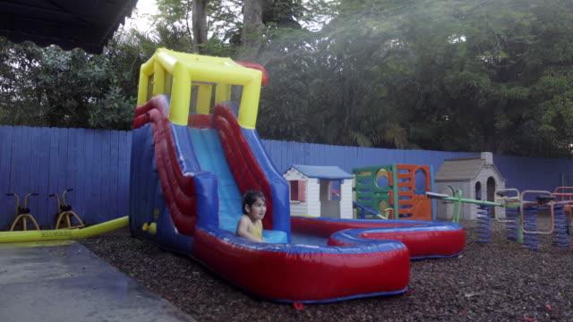 vídeos y material grabado en eventos de stock de niña jugando sola en tobogán de agua durante la pandemia de covid-19 - parvulario edificio escolar