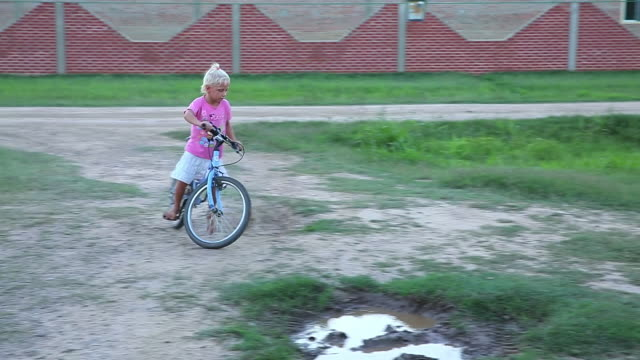 MS TS Little girl playing and cycling at garden area / Manitoba Community, Close to Santa Cruz de la Sierra, Bolivia
