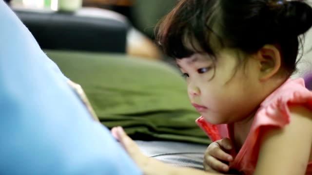 kleine mädchen spielen und berühren ein handy zu hause - kindertag stock-videos und b-roll-filmmaterial