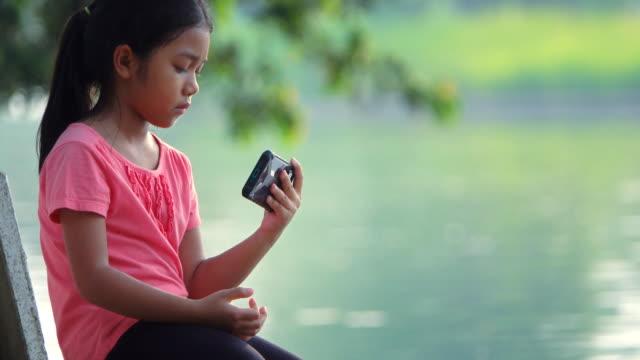 kleines mädchen spielt und berührt ein handy im park - kindertag stock-videos und b-roll-filmmaterial