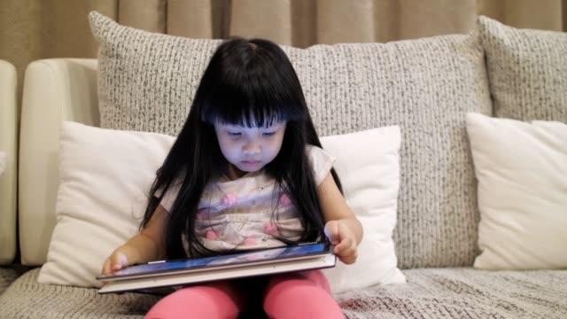 少女の再生とデジタル タブレット、スローモーションのオンライン メディアを見て - 民族衣装点の映像素材/bロール