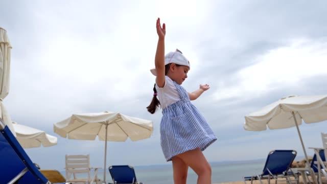 stockvideo's en b-roll-footage met klein meisje spelen rond en dansen op een winderig strand - haar naar achteren