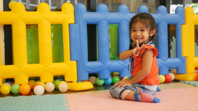 Kleine Mädchen spielen Ball in Spielplatz Raum, Victory-Zeichen