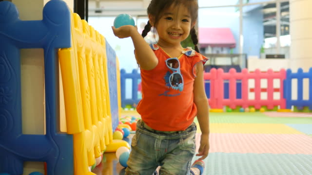 little girl playing ball in playground room - drive ball sports stock videos and b-roll footage