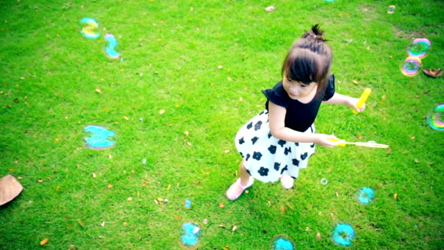 little girl playing bubbles slow motion - primary age child stock videos and b-roll footage