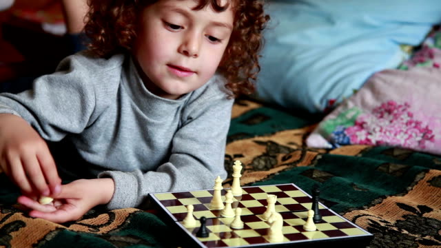 Little girl playing chess on the bed