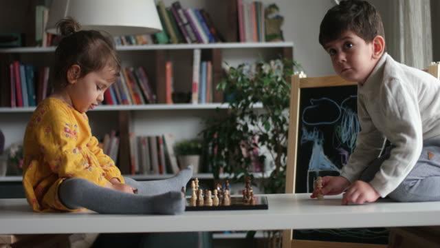弟とチェスをしている少女 - 余暇 ゲームナイト点の映像素材/bロール