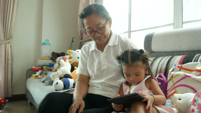 little girl playing digital tablet with grandmother