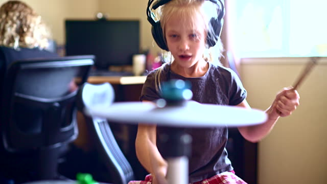 little girl playing drums when her sister doing homework - drum percussion instrument stock videos & royalty-free footage