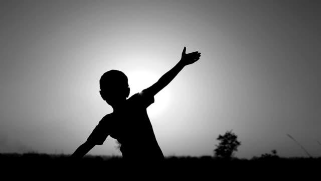 bambina giocare al tramonto - bianco e nero video stock e b–roll