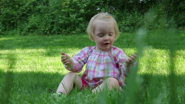 vidéos et rushes de petite fille jouant avec de l'herbe - vêtement de bébé
