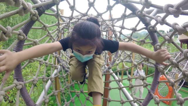 vídeos de stock e filmes b-roll de little girl playing in playground during the epidemic - higiene